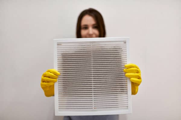 a woman holds a dirty air filter with gloves on