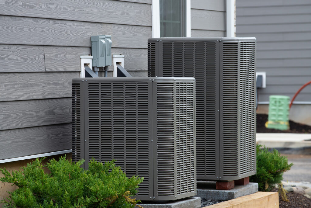 Two air conditioner units outside of a house