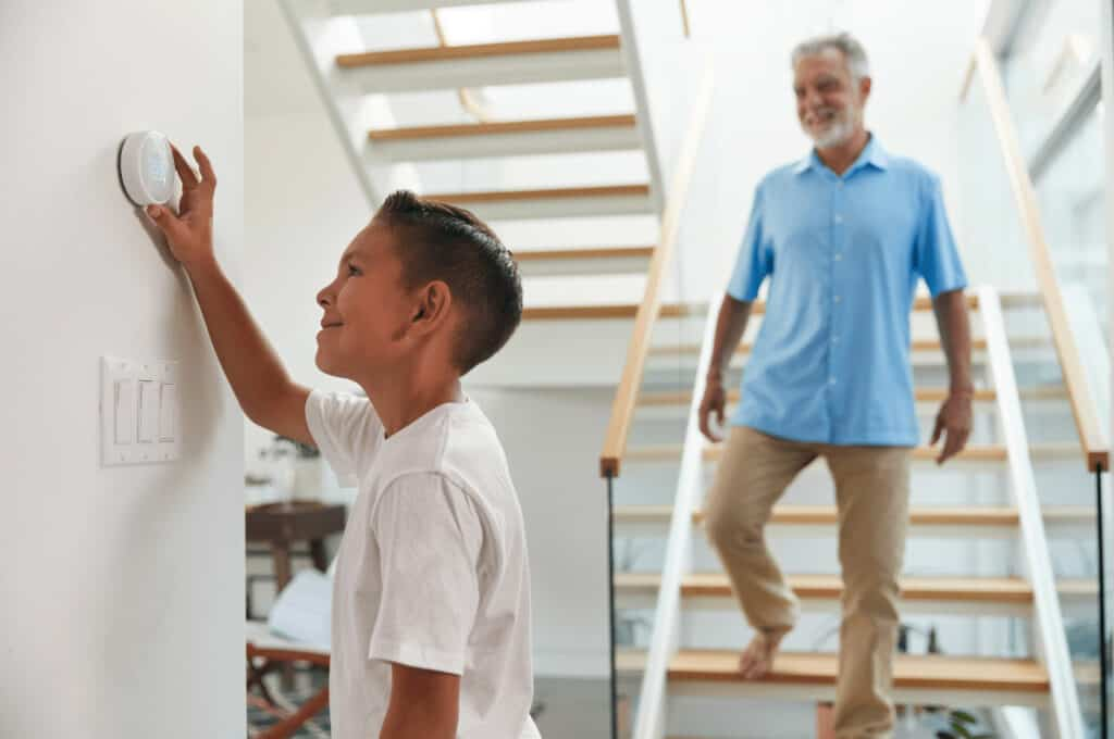 A young boy changes the home's thermostat and his father walks down the stairs