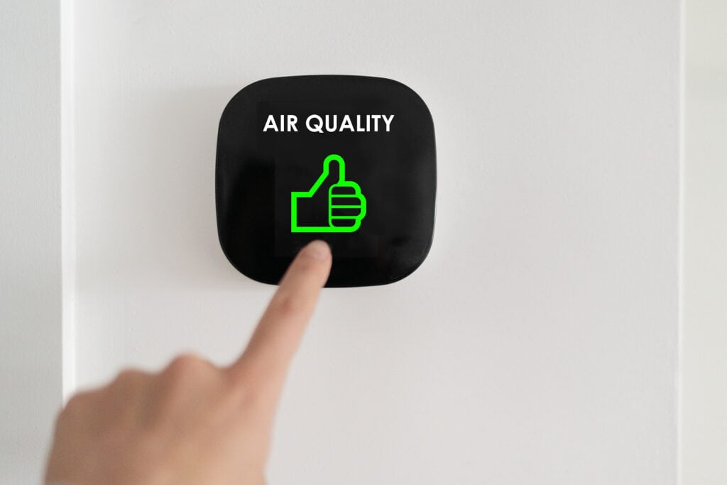 """A person points their finger to a device on their wall that shows a green thumbs up and text reading """"Air Quality"""""""