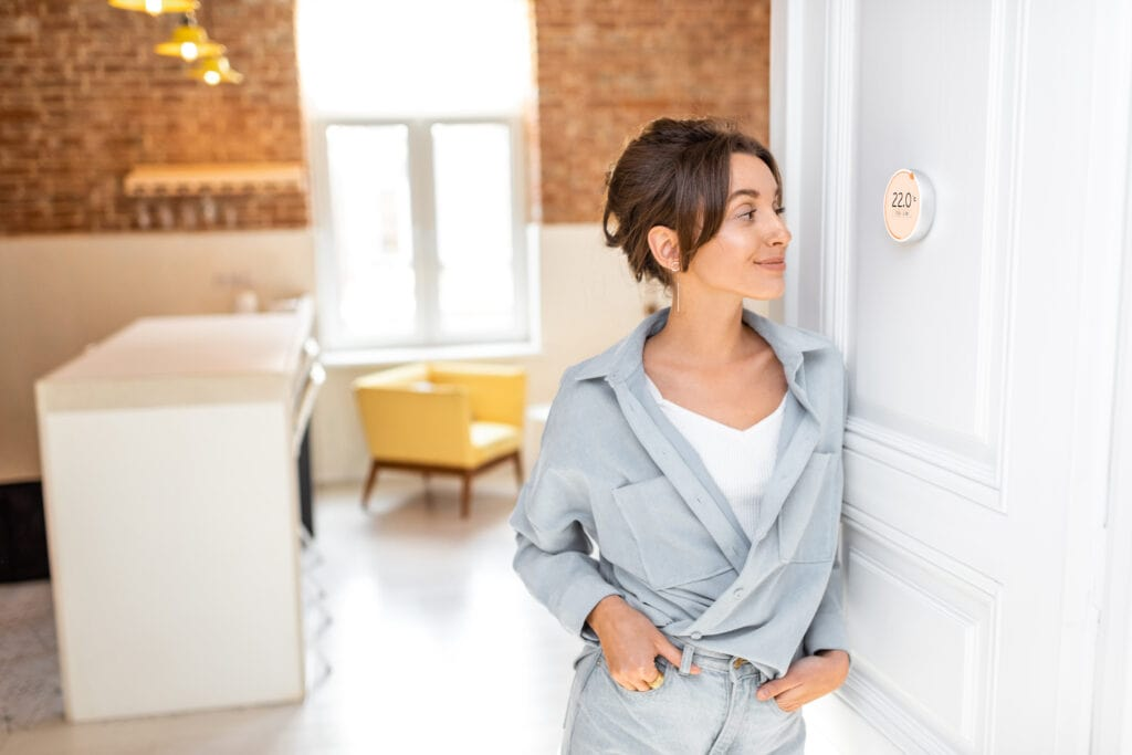 Woman regulating heating temperature with a modern wireless thermostat installed on the white wall at home.