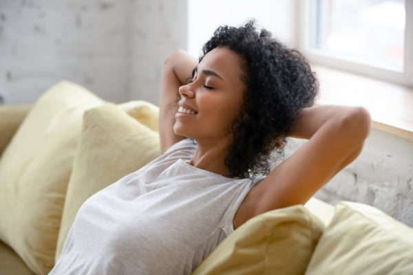 African American woman relax on comfortable couch at home