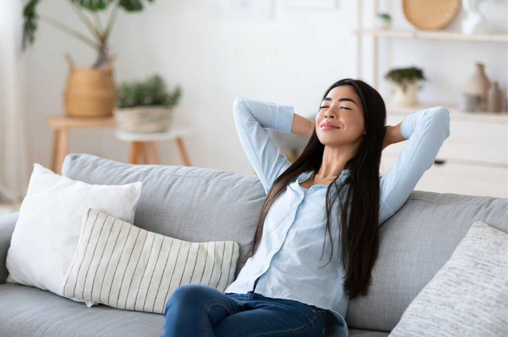 A woman relaxes on her couch