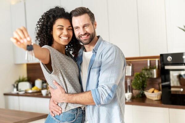 A young couple holds the house keys in their new home's kitchen