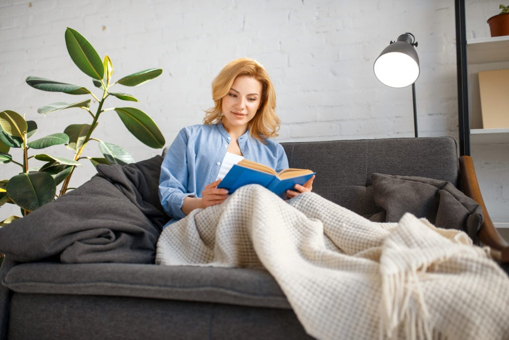Young woman under a blanket reading book on couch