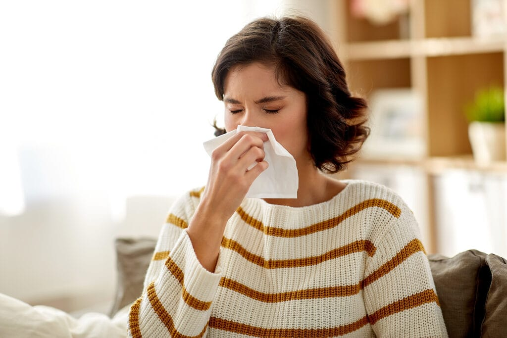 woman sneezing into tissue3