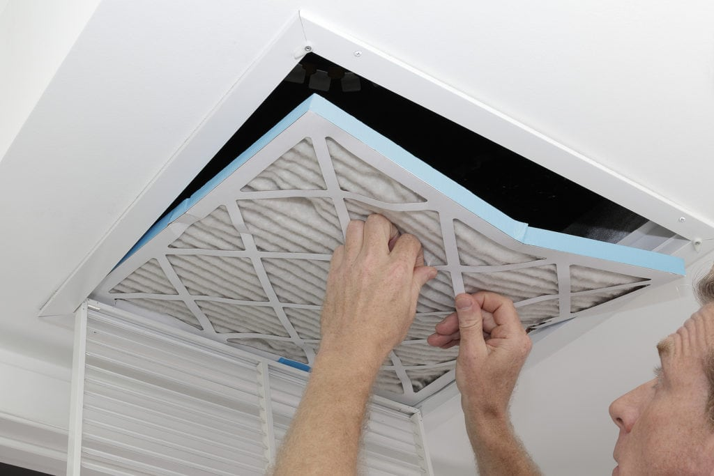 person removing dirty air filter from vent